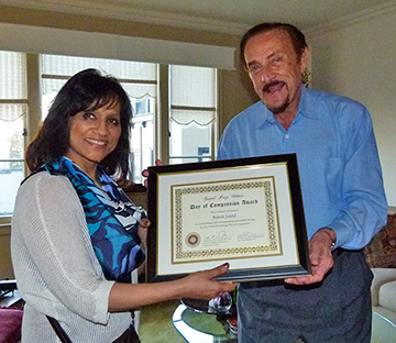 Balesh Jindal of New Delhi, India, a student in the Social Psychology MOOC, holds up her Day of Compassion Award with Stanford University Professor Emeritus Philip Zimbardo, a contributor to the MOOC. Jindal was the winner of a contest that asked students to live 24 hours ascompassionately as possible, and analyze the experience through a social psychology lens.