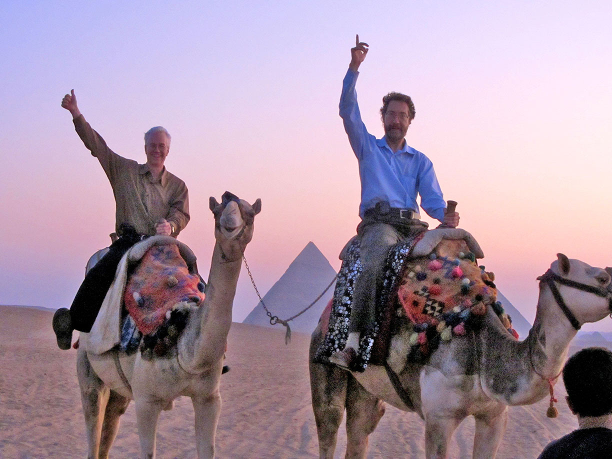 Banning Eyre '79 (l) and Sean Barlow '79 (r) enjoy a post-concert camel ride at sunrise, guests of Egyptian superstar Hakim.