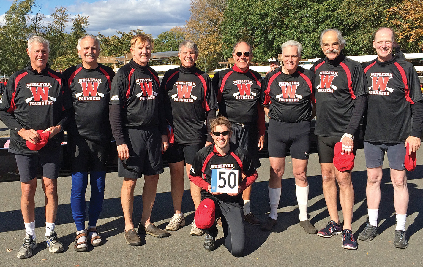Photographed at the 2015 Head of the Charles, the Founders Group of Wesleyan Crew find the sport has brought them enduring friendships (left to right): Harrison Knight '68, Joe Kelly Hughes '67, Bill Nicholson '68, Wally Murfiit '68, Bob Svensk '68, Will Macoy '67, John Lipsky '68, Nason Hamlin'68, and, kneeling, cox George Bennum '09.