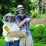 Beekeeper-herablist-artist Stephanie Bruneau '00 (here, with her husband, Emile), runs The Benevolent Bee, a small business selling honeybee hive-derived products.